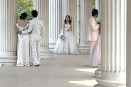 A bride waits for her groom as other couples pose for wedding photos at a park in Beijing, China, April 13, 2014. A new BMO InvestorLine study reveals that Canadians plan to spend an average of $15,000 on their weddings. THE CANADIAN PRESS/AP, Ng Han Guan
