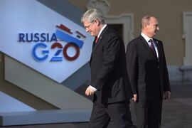 Canadian Prime Minister Stephen Harper walks past Russian President Vladimir Putin at the G20 Summit Thursday Sept.5, 2013 in St.Petersburg, Russia. The federal government says it will impose new sanctions against Russia in coming days over Moscow's support of rebel groups in Ukraine. THE CANADIAN PRESS/Adrian Wyld