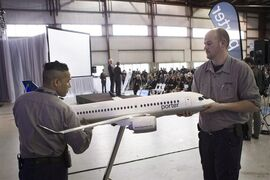 Porter employees position a model of a CS100 airplane at a news conference in Toronto on Wednesday April 10, 2013. Porter Aviation Holdings Inc. has signed a deal to sell its passenger terminal at Billy Bishop Toronto City Airport to Nieuport Aviation Infrastructure Partners GP, a consortium of infrastructure investors. THE CANADIAN PRESS/Chris Young