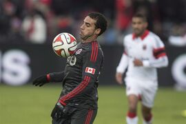 Toronto FC 's Dwayne DeRosario (left) controls the ball during first half MLS action against D.C. United in Toronto on Saturday March 22, 2014. De Rosario has been suspended for one game and fined for kicking out at a Montreal Impact player on the weekend THE CANADIAN PRESS/Chris Young