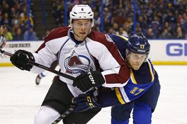 Colorado Avalanche's Erik Johnson, left, and St. Louis Blues' Jaden Schwartz battle for position during the first period of an NHL hockey game in St. Louis on Jan. 19, 2015. The Colorado Avalanche will be without top defenceman Erik Johnson for three to eight weeks due to a knee injury. THE CANADIAN PRESS/AP, Billy Hurst