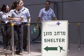 Israelis airport workers pass a sign pointing to a shelter for refuge in case a warning siren at Ben Gurion International airport in Tel Aviv. THE CANADIAN PRESS/AP, Dan Balilty