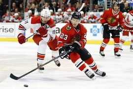 Chicago Blackhawks left wing Kris Versteeg (23) skates with the puck past Carolina Hurricanes center Jordan Staal (11) during the second period of an NHL hockey game on Monday, March 2, 2015, in Chicago. (AP Photo/Andrew A. Nelles)
