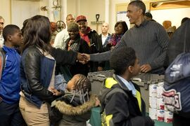 President Barack Obama shakes hands with a parton as he and his family distribute food at