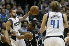 Dallas Mavericks guard J.J. Barea (5) passes to teammate Dirk Nowitzki (41) while being defended by Brooklyn Nets guard Markel Brown (22) during the first half of an NBA Basketball game Saturday, Feb. 28, 2015, in Dallas. (AP Photo/LM Otero)