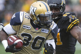 Hamilton Tiger Cats Brandon Bourdreux (right) chases down Winnipeg Blue Bombers Will Ford during first half CFL action in Hamilton on Saturday.