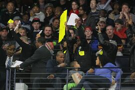Ferguson protestors walk inside the arena in the first period in an NBA basketball game of the Toronto Raptors at Atlanta Hawks in Atlanta, Wednesday, Nov. 26, 2014. (AP Photo/Todd Kirkland)