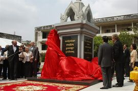 German Ambassador to Cambodia, Joachim Baron Von Marschall, left, pulls ribbon during an opening ceremony of the Memorial in Tuol Sleng Genocide Museum in Phnom Penh, Cambodia, Thursday, March 26, 2015. The memorial built at Toul Sleng Genocide Museum to remember at least 12,000 people tortured and killed there during the radical Khmer Rouge regime, has been official inaugurated Thursday. The letters on a memorial rads: Never will be forgot the crimes committed during the Democratic Kampuchea regime. (AP Photo/Heng Sinith)