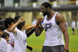 Israel Idonije greets a group of kids during his annual all-star football camp in Winnipeg. Idonije has decided to retire from football after 11 seasons in the NFL.