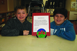 Luxton School students Lucas Pistun (left) and Cayden Laithlin display one of the valentines the class created for Deer Lodge Centre residents.