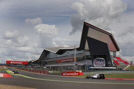 """FILE - This is a Sunday, July 6, 2014 file photo of Finland's Valtteri Bottas of William, bottom right, as he drives his car past the Wing corporate building to gain second place during the British Formula One Grand Prix at Silverstone circuit, Silverstone, England. Work has started Wednesday April 1, 2015 on repairing the roof of the Silverstone motor racing circuit which was damaged by high winds in recent days. Part of the """"Wing"""" _ the $40 million, three-story corporate building at the host venue of Formula One's British Grand Prix, was affected by the winds on late Sunday and Monday. (AP Photo/Jon Super, File)"""