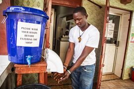 FILE - In this Sept. 14, 2014, file photo, a man dries his hands after washing them with chlorine outside a shop in the city of Freetown, Sierra Leone. Six months into the biggest-ever Ebola outbreak, scientists say they've learned more about how the potentially lethal virus behaves and how future outbreaks might be stopped. The first cases of Ebola were reported in Guinea by the World Health Organization on March 23 before spreading to Sierra Leone, Liberia and elsewhere. (AP Photo/ Michael Duff, File)