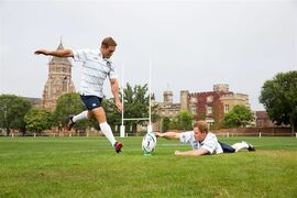 In this photo taken Wednesday Sept. 17, 2014 Britain's Prince Harry, right, holds the ball as former England Rugby star Jonny Wilkinson makes a punt during a photocall at the Rugby School, in Rugby central England. With one year to go until the start of the Rugby World Cup 2015, Prince Harry has been appointed as Honorary President of England Rugby 2015. (AP Photo/ David Davies/PA) UNITED KINGDOM OUT NO SALES NO ARCHIVE