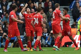 Liverpool's Philippe Coutinho, second left, celebrates scoring during their English Premier League soccer match against Queens Park Rangers at Loftus Road, London, Sunday, Oct. 19, 2014. (AP Photo/Tim Ireland)