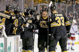 Boston Bruins left wing Milan Lucic, center, is congratulated by teammates including Zdeno Chara (33) and Zach Trotman (62) after scoring his first of two goals during the first period of an NHL hockey game against the New York Rangers, Saturday, March 28, 2015, in Boston. (AP Photo/Mary Schwalm)