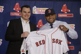 Newly acquired Boston Red Sox free agent third baseman Pablo Sandoval smilies as he and Red Sox general manager Ben Cherington pose with a team jersey as Sandoval is introduced to the media at Fenway Park Tuesday, Nov. 25, 2014 in Boston. (AP Photo/Stephan Savoia)