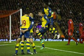 Arsenal's Olivier Giroud, lower centre, celebrates with jubilant teammates after scoring during the English Premier League soccer match between Liverpool and Arsenal at Anfield Stadium, Liverpool, England, Sunday Dec. 21, 2014. (AP Photo/Jon Super)