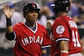 Cleveland Indians' Jose Ramirez, left, is congratulated by teammate Carlos Santana, right, after scoring the go-ahead run from third off a Michael Brantley single in the 11th inning of a baseball game against Kansas City Royals in Kansas City, Mo., Saturday, Aug. 30, 2014. (AP Photo/Colin E. Braley)