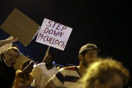 Protesters march Thursday, Aug. 21, 2014, in Ferguson, Mo. Protesters again gathered Thursday evening, walking in laps near the spot where Michael Brown was shot. Some were in organized groups, such as clergy members. More signs reflected calls by protesters to remove the prosecutor, Robert McCulloch, from the case. (AP Photo/Jeff Roberson)