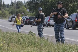 Self-proclaimed Donetsk People's Republic policemen guard a convoy of international forensic experts, Dutch and Australian policemen and members of the Organization for Security and Cooperation in Europe mission in Ukraine, as it approached Shakhtarsk, Donetsk region, eastern Ukraine, on Monday, July 28, 2014. An international police team abandoned its attempt to reach the crash site of a Malaysia Airlines plane for a second day running Monday as clashes raged in a town on the road to the area. (AP Photo/Dmitry Lovetsky)