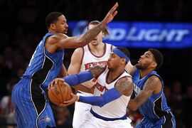 New York Knicks' Carmelo Anthony (7) looks to pass away from a double-team by Orlando Magic's Channing Frye, left, and Devyn Marble during the third quarter of an NBA basketball game Friday, Jan. 23, 2015, in New York. New York won 113-106. (AP Photo/Jason DeCrow)