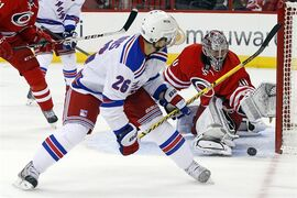 New York Rangers' Martin St. Louis (26) has his shot blocked by Carolina Hurricanes goalie Cam Ward (30) during the first period of an NHL hockey game in Raleigh, N.C., Tuesday, March 11, 2014. (AP Photo/Karl B DeBlaker)
