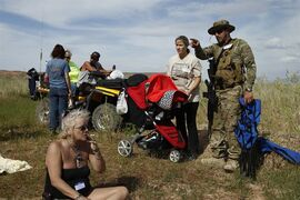 Steven Scalzo, right, and his wife Jamie Scalzo look for a place to set up their chairs during a rally in support of Cliven Bundy along the Virgin River near Bunkerville, Nev. Friday, April 18, 2014. (AP Photo/Las Vegas Review-Journal, John Locher)