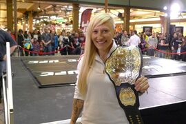 Olympic bobsled champion Kaillie Humphries poses with a UFC championship belt at a public workout in Quebec City on Sunday, April 13, 2014. Humphries tried her hand at mixed martial arts Sunday, working out with renowned coach Firas Zahabi and two top UFC fighters. THE CANADIAN PRESS/Neil Davidson