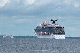 FILE - The cruise ship Carnival Magic passes near Cozumel , Mexico, in this Friday, Oct. 17, 2014 file photo. The Coast Guard said it has retrieved a blood sample from a Dallas health care worker who is aboard a cruise ship and being monitored for signs of Ebola. Petty Officer Andy Kendrick says the crew flew in a helicopter Saturday Oct. 18, 2014 to meet the Carnival Magic and lowered a basket of supplies. The woman provided a sample. (AP Photo/Angel Castellanos, File)