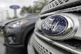 In this Monday, Jan. 12, 2015 photo, Ford vehicles sit on the lot at a car dealership, in Brandon, Fla. Ford says it will take an $800 million charge in the fourth quarter because of exchange rate problems between the Venezuelan bolivar and the U.S. dollar. (AP Photo/Chris O'Meara)