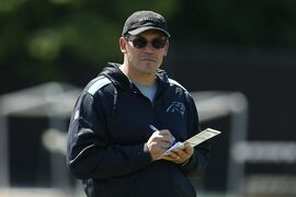 "FILE - This May 16, 2014, file photo, shows Carolina Panthers head coach Ron Rivera looking on at his players during an NFL football rookie minicamp in Charlotte, N.C. Rivera and quarterback Cam Newton seem more focused on the big picture: getting the Panthers to the playoffs in back-to-back seasons for the first time, and winning a postseason game for the first time since 2005. ""Status quo isn't good enough,"" Rivera said. (AP Photo/Chris Keane, File)"