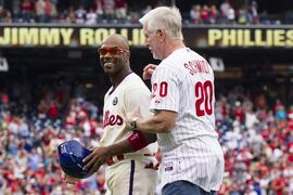 FILE - This June 14, 2014, file photo shows Philadelphia Phillies' Jimmy Rollins, left, celebrating his single with former Phillies' Mike Schmidt, right, during the fifth inning of a baseball game against the Chicago Cubs in Philadelphia. The single gave Rollins the all time hits mark for the Phillies, passing the mark held by Schmidt. The Phillies have finalized their trade of Jimmy Rollins, sending the All-Star shortstop and cash to the Los Angeles Dodgers for right-hander Zach Eflin and left-hander Tom Windle. The deal was agreed to last week at the winter meetings and announced Friday, Dec. 19, 2014, a day after the Dodgers completed a trade that sent slugging outfielder Matt Kemp to San Diego. (AP Photo/Chris Szagola)