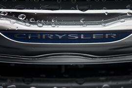 In this Dec. 2, 2014 photo, a Chrysler minivan sits under rain at a car lot in San Diego. Major automakers report vehicle sales for February on Tuesday, March 3, 2015. (AP Photo/Gregory Bull)