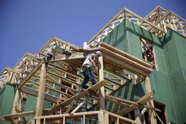 A builder works on the construction of new homes in Belmar, N.J. on July 30, 2014. THE CANADIAN PRESS/AP, Mel Evans