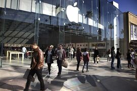 In this Saturday, Jan. 3, 2015 photo, shoppers walk by the Apple Store along the the Third Street Promenade in Santa Monica, Calif. Apple Inc. reports quarterly financial results on Tuesday, Jan. 27, 2015. (AP Photo/Richard Vogel)