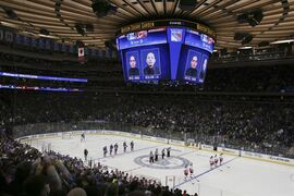 Spectators and players observe a moment of silence in tribute to NYPD police officers Rafael Ramos and Wenjian Liu as their likenesses are displayed on the jumbotron before an NHL hockey game between the New York Rangers and Carolina Hurricanes, Sunday, Dec. 21, 2014, in New York. (AP Photo/John Minchillo)