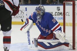 New York Rangers goalie Henrik Lundqvist (30) makes a save during the first period of their preseason NHL hockey game against the New Jersey Devils, Monday, Sept. 22, 2014, in New York. (AP Photo/John Minchillo)