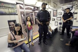 A couple of police officers ride the shuttle between New York's Times Square and Grand Central Station, Friday, Sept. 9, 2011. Just days before the 10th anniversary of the Sept. 11 attacks, U.S. counterterrorism officials are chasing a credible but unconfirmed al-Qaida threat to use a car bomb on bridges or tunnels in New York City or Washington. (AP Photo/Mary Altaffer)