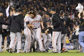 The San Francisco Giants swarm around starting pitcher Madison Bumgarner, center, after he pitched a four-hitter against the Pittsburgh Pirates in the NL wild-card playoff baseball game Wednesday, Oct. 1, 2014, in Pittsburgh. The Giants won 8-0. (AP Photo/Don Wright)