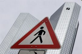 A traffic sign stands near the headquarters of the Deutsche Bank in Frankfurt, Germany, Saturday, April 25, 2015. Deutsche Bank AG says it plans to