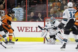 Philadelphia Flyers' Michael Raffl, left, of Austria, scores a goal past San Jose Sharks' Alex Stalock, center, as Patrick Marleau looks on during the first period of an NHL hockey game, Saturday, March 28, 2015, in Philadelphia. (AP Photo/Matt Slocum)