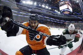 Philadelphia Flyers' Zac Rinaldo, left, and Minnesota Wild's Thomas Vanek, right, of Austria, battle for the puck during the first period of an NHL hockey game, Thursday, Nov. 20, 2014, in Philadelphia. (AP Photo/Matt Slocum)