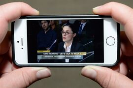 A viewer watches a live stream of Netflix global public policy director Corie Wright testifying before the CRTC on Friday September 19, 2014. THE CANADIAN PRESS/Sean Kilpatrick