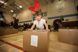 Three-year-old Rain Fata helps move boxes during the 12th annual Ma Mawi Wi Chi Itata Centre Christmas Food Hamper drive at R.B. Russell School in Winnipeg.