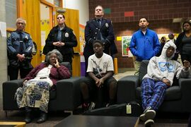 Citizens and police officers gather at the Garfield Community Center in Seattle Monday, Nov. 24, 2014, to watch the announcement on television that a grand jury decided Ferguson police officer Darren Wilson will not be indicted on charges in the shooting death of unarmed black teenager Michael Brown. Bottom left is Rev. Harriett Walden, of the group