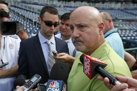 FILE - In this July 31, 2014 file photo, Washington Nationals general manager Mike Rizzo pauses while speaking to reporters before a baseball game against the Philadelphia Phillies at Nationals Park in Washington. Two years after famously being shut down by the Washington Nationals to protect his elbow, Stephen Strasburg finally will make his postseason debut this week for the NL East champions.