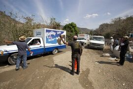In this Feb. 11, 2015 photo, community police set up a roadblock controlling who enters and leaves Nuevo Balsas. in the Guerrero state of Mexico. In Guerrero and elsewhere, businesses complain they are losing merchandise to highway hijackings. Anti-government protesters have commandeered toll-booths, sacked government offices, blocked shipments and shut down airports. Drug cartels rule large swaths of land, extorting business owners, buying off authorities and disrupting important industries such as agriculture and tourism. (AP Photo/Eduardo Verdugo)