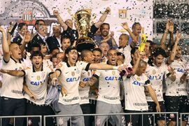 Corinthians' players celebrate with the trophy at end of the final match of the Sao Paulo State soccer league against Santos, in Santos, Brazil, Sunday, May 19, 2013. Corinthians won 3-2 on aggregate. (AP Photo/Andre Penner)