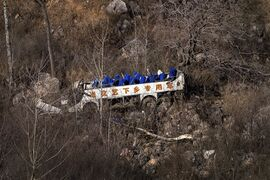 The remains of a bus is seen after it fell off a cliff in Linzhou in central China's Henan province Tuesday, March 3, 2015. The bus carrying an opera troupe fell off a cliff on Tuesday, killing and injuring more than a dozen people, state media reported. (AP Photo) CHINA OUT