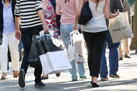 FILE - In this June 6, 2014 file picture persons walk with shopping bags in Hamburg, Germany. A closely-watched survey shows economic expectations among German consumers have